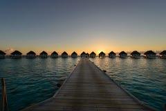 Moment de coucher du soleil au lieu de villégiature luxueux, passage couvert en bois aux Bu de villa de l'eau photographie stock libre de droits