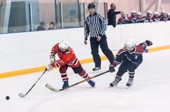 Moment de jeu des équipes de glace-hockey d'enfants Image libre de droits