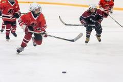 Moment de jeu des équipes de glace-hockey d'enfants Photographie stock libre de droits