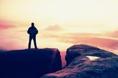 Moment der Einsamkeit Mann auf den Felsenreichen und Uhr über dem nebelhaften und nebeligen Morgental zu Sun Lizenzfreies Stockfoto