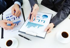 Moment of explanation. Hands of business people working with documents stock photo