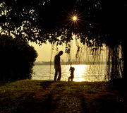 A moment of father and his son. Silhouette of parent and his child spend their moment during evening at a park Stock Images
