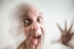 Moment of fury. Blurred man suffering from dementia and insanity, opened hand, screaming, in moment of fury, hallucination stock photography
