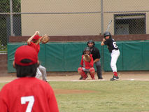 The moment of the game. Junior team in action. The moment of baseball game. Pitcher is throwing the ball. Catcher and hitter on position. Teamwork Royalty Free Stock Image