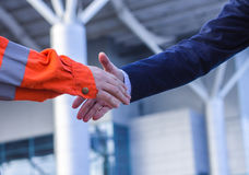 Moment before handshake of suit and boilersuit. Royalty Free Stock Photos