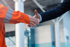 Moment before handshake of suit and boilersuit Royalty Free Stock Images