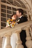 Moment of happiness. Groom embracing his bride on the theater stairs royalty free stock photos