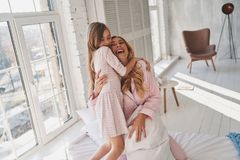 Moment of happiness. Top view of cute little girl bonding with h. Er mother and smiling while spending time at home Stock Photography