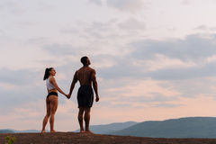 Moment of harmony. Happy mixed race couple athlethic caucasian woman with african american bodybuilde holding hands and Royalty Free Stock Photography