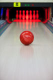 Moment when the heart stops beating. Close-up of bright red bowling ball rolling along bowling alley Royalty Free Stock Images