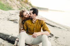 A moment before a kiss. Young couple is having fun and hugging on the beach. Beautiful girl embrace her boyfriend from. A moment before a kiss. Young couple is Royalty Free Stock Photos