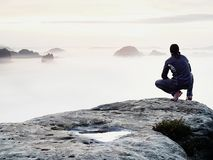 Moment of loneliness on exposed rocky summit. Man in black enjoy marvelous view. Hiker sit on the peak Stock Image