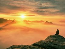 Moment of loneliness on exposed rocky summit. Man in black enjoy marvelous view. Hiker sit on the peak. Of rock and watching into colorful mist and fog in Royalty Free Stock Photo