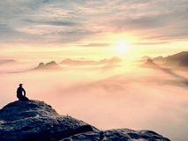 Moment of loneliness on exposed rocky summit. Man in black enjoy marvelous view. Hiker sit on the peak. Of rock and watching into colorful mist and fog in Royalty Free Stock Images