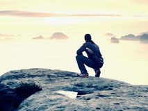 Moment of loneliness on exposed rocky summit. Man in black enjoy marvelous view. Hiker sit on the peak Stock Photo