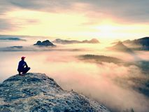 Moment of loneliness on exposed rocky summit. Man in black enjoy marvelous view. Hiker sit on the peak Royalty Free Stock Images