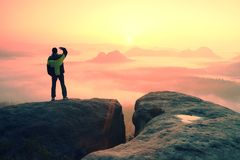 Moment of loneliness. Man on the rock empires  and watch over the misty and foggy morning valley to Sun Royalty Free Stock Images