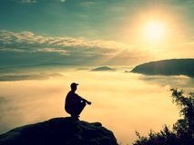 Moment of loneliness. Man sit on rock and watching into colorful mist and fog in valley. Stock Photos