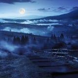 Moment - ner till byn i dimmiga berg på natten Arkivbild
