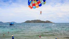 Moment of parasailer take off from beach over sea into sky. NHA TRANG, KHANH HOA/VIETNAM - SEPTEMBER 11 2015: Moment of take off of parasailer from land and fly stock video