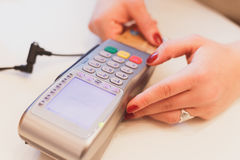 Moment of payment with a credit card through terminal. Woman hand with credit card swipe through terminal for sale in restaurant Royalty Free Stock Image