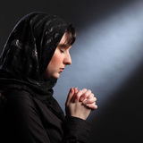 Moment of quiet faith as young woman prays. Faith of young religious woman wearing black hijab headscarf, eyes closed and hands together in prayer Stock Photos