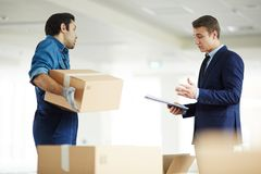 Moment of relocation. Confident businessman reading list of things that should have been delivered to new office and discussing it with worker of relocation Stock Images