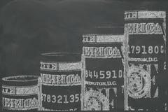 Moment som göras av en dollar, rullar på den svarta svart tavlan Royaltyfri Foto