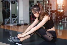 Moment sportif convenable de jeune femme pour attacher ses chaussures, attachant son shoel photo stock