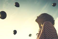 Moment surréaliste, femme semblant étonnée avec une pluie des boules noires tombant du ciel image stock