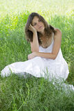 A moment to think. Beautiful young woman thinking about something, sitting in a meadow Stock Photography