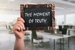 The moment of truth on chalkboard. A woman holding wooden blackboard with text the moment of truth ,office background royalty free stock images