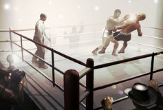 Moment of  victory. On a ring surrounded by several persons, a boxer knocks out his opponent   under the attentive glance of the  referee Stock Images