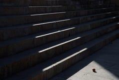 Momenten av stentrappuppgången som är upplysta vid en stråle av solen, i grunden av stegen, är en orange apelsin Royaltyfria Bilder