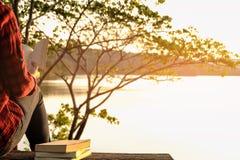 Momenti di rilassamento, giovane donna che legge un libro nel fondo della natura Rilassamento solo, colore del tono dei pantaloni Fotografie Stock