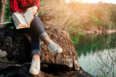 Momenti di rilassamento, giovane donna che legge un libro nel fondo della natura Rilassamento solo, colore del tono dei pantaloni Immagine Stock