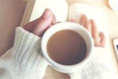 Momenti di rilassamento, tazza di caffè e un libro sulla tavola di legno nel fondo della natura, colore del tono d'annata e fuoco Fotografie Stock