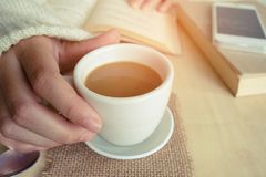 Momenti di rilassamento, tazza di caffè e un libro sulla tavola di legno nel fondo della natura, colore del tono d'annata e fuoco Immagini Stock