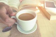 Momenti di rilassamento, tazza di caffè e un libro sulla tavola di legno nel fondo della natura, colore del tono d'annata e fuoco Immagine Stock