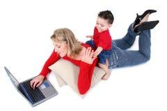 Momento adorabile della famiglia con la madre ed il figlio al computer portatile Immagine Stock