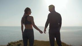 Momento da harmonia, par de amor desportivo que guarda as mãos que olham o por do sol na posição da água na montanha junto sobre filme
