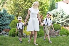 Momento da vida da família feliz! Uma mãe nova e dois filhos novos para uma caminhada no parque fotografia de stock royalty free