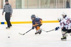 Momento de juego entre los equipos del hielo-hockey de los niños Imagenes de archivo