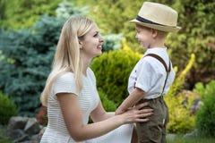 ?Momento de la vida de familia feliz! Ni?o de la madre y del hijo que juega divirti?ndose junto en la hierba en d?a de verano sol fotografía de archivo