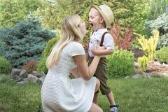 ?Momento de la vida de familia feliz! Ni?o de la madre y del hijo que juega divirti?ndose junto en la hierba en d?a de verano sol foto de archivo