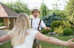 ?Momento de la vida de familia feliz! Ni?o de la madre y del hijo que juega divirti?ndose junto en la hierba en d?a de verano sol imagen de archivo