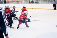 Momento del juego de equipos del hielo-hockey de los niños Fotos de archivo