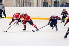Momento del juego de equipos del hielo-hockey de los niños Foto de archivo libre de regalías