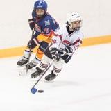 Momento del juego entre los equipos del hielo-hockey de los niños Fotos de archivo libres de regalías