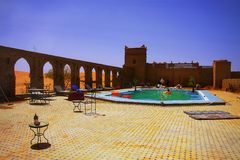 Momento do abrandamento em um deserto marroquino dos amids da piscina do hotel, com as dunas de areia no horizonte Fotos de Stock